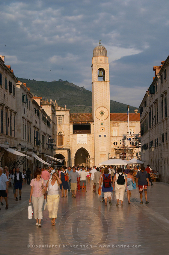 The main street Stradun Placa with traditional houses and flocks of tourists, view over clock tower and loggia on the central square in evening sunlight Dubrovnik, old city. Dalmatian Coast, Croatia, Europe.