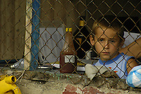 A local boy in Sevegre, Costa Rica peers out from his home.