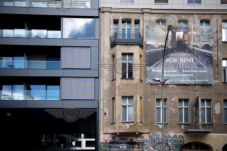 A banner advertises a house for rent at 36 Chausseestrasse beside an modern block in Mitte.