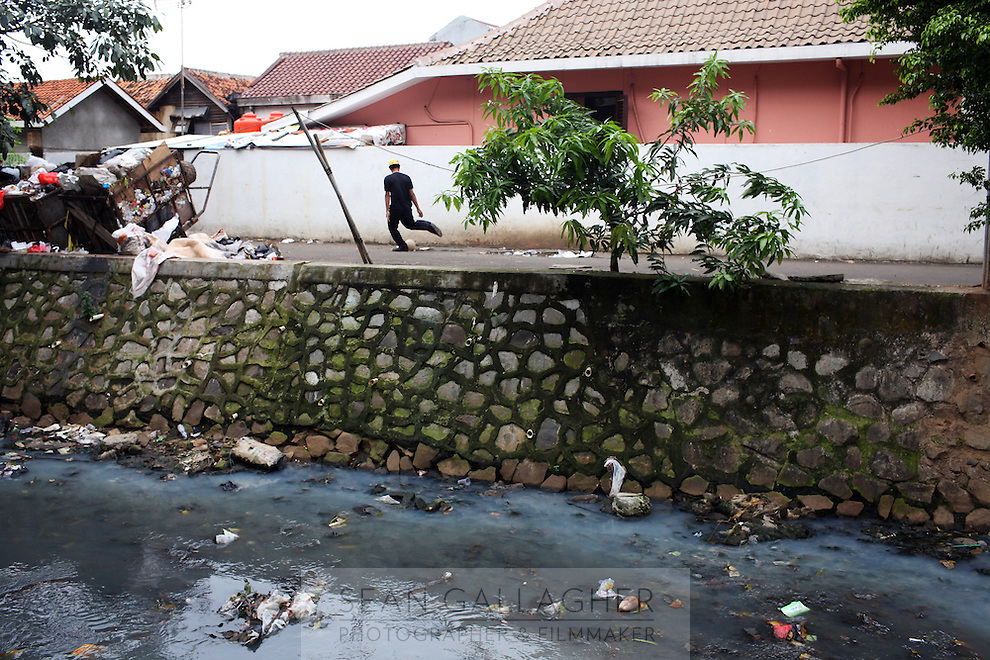 A man plays football on a road near to a heavily polluted river in central Jakarta. All of the city's waterways suffer from severe water pollution as refuse and human waste is readily disposed off into the urban area's rivers and streams.