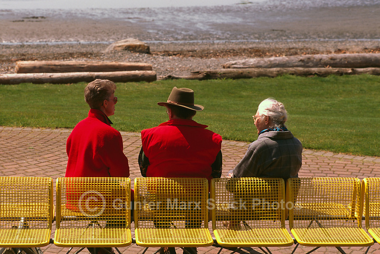 Three Senior People sitting on a Bench along Seaside Promenade Walkway and Semiahmoo Bay, White Rock, BC, British Columbia, Canada