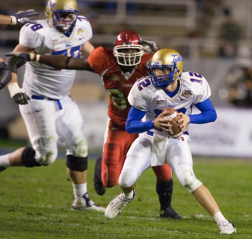 23 December 2006: Tulsa quarterback Paul Smith (#12) dodges Utah defenders while running with the ball during the 2006 Bell Helicopters Armed Forces Bowl between The University of Tulsa and The University of Utah at Amon G. Carter Stadium in Fort Worth, TX.
