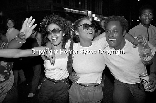 Notting Hill Carnival group of black men and women celebrating partying, having fun dancing into the night. 1980s  UK