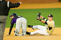 Chris Kontos #2 of the Northwestern Wildcats slides into second base safely ahead of the tag by Conor Keniry #14 of the Wake Forest Demon Deacons at Gene Hooks Field on February 26, 2011 in Winston-Salem, North Carolina.  Photo by Brian Westerholt / Four Seam Images