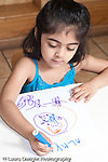 Education Preschool 3-5 year olds art activity girl drawing recognizable shapes using markers writing letters of her name vertical