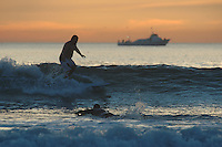 Pacific Beach, San Diego, California, USA:  Monday, January 19 2009.  A surfer enjoys the swell that arrived on San Diego's shores just in time for the MLK holiday.  The holiday was marked by warm weather, big surf and a technicolored sunset in San Diego as much of the rest of the country shivered in the cold.