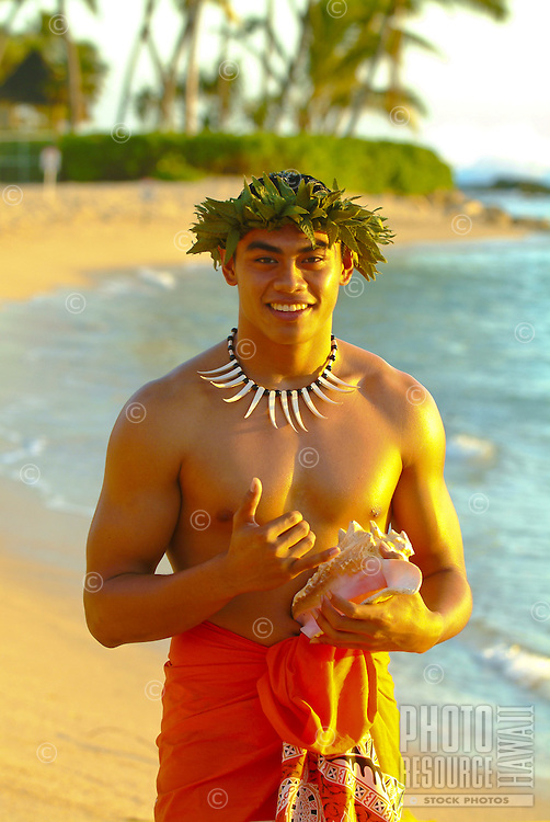 Hawaiian man wearing a head lei and necklace, holds a conch shell (used by early Hawaiians as a means of communication) and gives the shaka sign with his hand. Paradise Cove Luau, Ko Olina