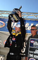 Oct. 30, 2011; Las Vegas, NV, USA: NHRA pro stock driver Jason Line (left) is presented the 2011 pro stock world championship trophy by NHRA president Tom Compton at the Big O Tires Nationals at The Strip at Las Vegas Motor Speedway. Mandatory Credit: Mark J. Rebilas-