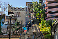 """Switzerland. Canton Ticino. Lugano. Tourists walk up and down the stairs close to the old """"Funicular degli Angioli. The Funicular degli Angioli (Italian: Funicolare degli Angioli) was a funicular railway and inclined lift in the city of Lugano. It linked a lower terminus near the lakeside and the church of Santa Maria degli Angioli with an upper terminus adjacent to the Hotel Bristol. The upper station was on the third floor of a tower, linked with a footbridge to the hotel. The line had a single track and single car, which was balanced by a vertically operating counterweight in the tower. When in operation, the line was 142 metres in length and climbed a vertical distance of 53 metres with a maximum gradient of 44% and an average gradient of 38.7%. The line opened in 1913. In 1973 it was gifted by its owner to the City of Lugano. The Hotel Bristol closed in 1981, and the funicular followed in 1986. The line remains in existence, but in an abandoned state. In 2012 the line was listed as a cultural property of regional significance. It is estimated that restoration  would cost CHF2.6 million. 30.12.2018 © 2018 Didier Ruef"""
