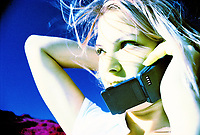 Photo of a woman talking on cell phones, woman, phone, hands.
