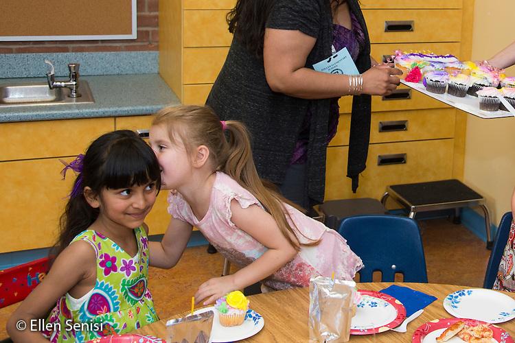 MR / Schenectady, NY. Zoller Elementary School (urban public school). Kindergarten classroom. Student (girl, 5) whispers to her friend (girl, 6, biracial) at classroom birthday party. MR: Myk2, Stu1. ID: AM-gKw. © Ellen B. Senisi.