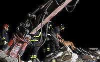 Firefighters and a detection dog work on rubble of collapsed buildings in the village of Amatrice, central Italy, hit by a magnitude 6 earthquake at 3,36 am, 24 August 2016.<br /> Vigili del Fuoco con un cane da soccorso al lavoro tra le macerie degli edifici crollati dopo il terremoto che alle 3,36 del mattino ha colpito Amatrice, 24 agosto 2016.<br /> UPDATE IMAGES PRESS/Isabella Bonotto