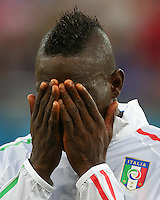 Mario Balotelli of Italy wipes his face during the team line ups