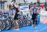 26 AUG 2012 - STOCKHOLM, SWE - Jonathan Brownlee (GBR) of Great Britain (right) watches as leader Steffen Justus (GER) of Germany (left) prepares to exit transition for the start of the bike during the 2012 ITU Mixed Relay Triathlon World Championships in Gamla Stan, Stockholm, Sweden. Justus and his German team lost the lead to the British team when Justus skidded twice during his bike leg  (PHOTO (C) 2012 NIGEL FARROW)