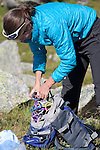 A woman climber bundles carabiners, assembling climbing gear on the Plan D'Aiguille, midway up the mountain from Chamonix to the Aiguille du Midi, Chamonix-Mont-Blanc, France