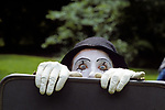 Mime performing climbing out of suitcase with white face and gloves Seattle Washington State USA