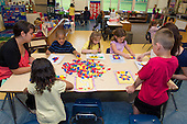 MR / Schenectady, NY. Zoller Elementary School (urban public school). Kindergarten inclusion classroom. Teacher and student teacher work at table with students and pattern block activity at math learning center time. MR: She4, War15. ID: AM-gKw. © Ellen B. Senisi.
