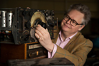 BNPS.co.uk (01202) 558833. <br /> Pic: CorinMesser/BNPS<br /> <br /> Pictured: Richard Bromell of Charterhouse Auctioneers with an aircraft radio, c1941. <br /> <br /> Radio Ga-Ga..<br /> <br /> A vast collection of vintage radios, televisions and record players have emerged for sale at auction following the death of their owner.<br /> <br /> The group, which consists of hundreds of old-school electronics, was amassed over several decades by an eccentric and dedicated collector.<br /> <br /> An electrician by trade, he housed the goods in a private museum near Dorchester in Dorset but rarely displayed them to the general public.