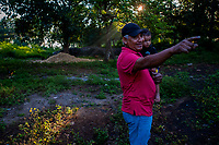 Miguel Ventura, a Salvadoran natural indigo producer, carries a baby boy while walking in the early morning in his farm near San Miguel, El Salvador, 12 November 2016. For centuries, indigo, a natural deep blue dye extracted from the leaves of tropical plants (Indigofera), has been known to the native indigenous inhabitants of Central America who used the blue tincture to color their fabrics and pottery. Although demand for natural indigo dropped significantly at the end of 19th century when a synthetic indigo was firstly introduced, commercialization of natural indigo has risen again during the last decades. Small-scale indigo farms, processing the crop on sustainable and ecological basis, are growing throughout the country, returning El Salvador to the place of the main natural indigo producer in Latin America.