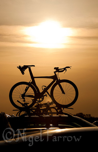 16 MAY 2010 - LYDD, GBR - Bikes sit in racks on the roofs of cars whilst competitors register before The Marshman Triathlons .(PHOTO (C) NIGEL FARROW)