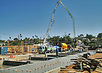 Large crane-like cement pumper pouring foundations at new home construction site.