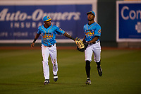 Lansing Lugnuts outfielders Reggie Pruitt (5) and DJ Neal (7) jog off the field between innings of a Midwest League game against the Beloit Snappers at Cooley Law School Stadium on May 4, 2019 in Lansing, Michigan. The Lugnuts wore their Copa de la Diversión jerseys, becoming the Lansing Locos for the evening. Beloit defeated Lansing 2-1. (Zachary Lucy/Four Seam Images)