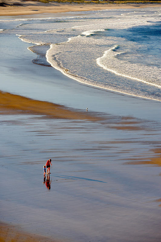 Mother and child walking at Cape Kiwanda. Oregon