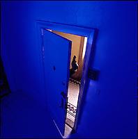 Hand with gun poking through partially open door<br />