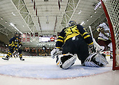 Matt Price (BC - 25) and Pat Bowen (Merrimack - 4) watch as the puck  heads across behind Joe Cannata (Merrimack - 35) after hitting the post. - The Boston College Eagles defeated the Merrimack College Warriors 4-3 on Friday, October 30, 2009, at Conte Forum in Chestnut Hill, Massachusetts.