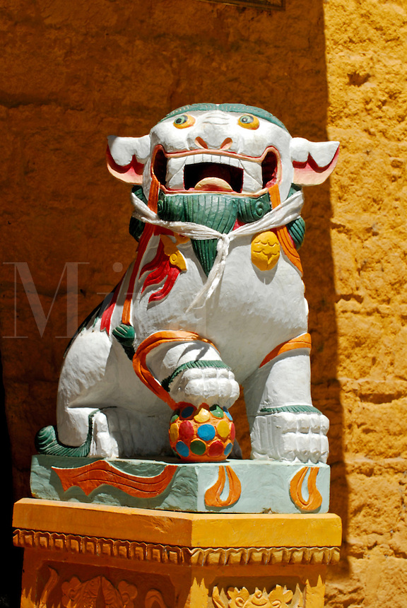 Tibetan national symbol of fearless joy, a now forbidden snow lion with paw on ball, guards the entrance to the Takten Migyur Potrang, or New Summer Palace of the 14th Dalai Lama, at Norbulingka, founded by the 7th Dalai Lama in 1755, Lhasa, Tibet, China.