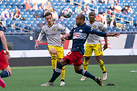 FOXBOROUGH, MA - MAY 16: Pedro Santos #7 Columbus SC passes the ball downfield as Teal Bunbury #10 of New England Revolution comes in to tackle during a game between Columbus SC and New England Revolution at Gillette Stadium on May 16, 2021 in Foxborough, Massachusetts.