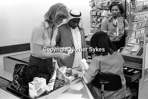 Arabs London UK 1977. Middle Eastern people came to Britain for subsidised health care in Harley Street clinics. . They mainly stayed in cheap hotels in Earls Court. Arab man Earls Court supermarket  two check out women help him with shopping and paying the bill.