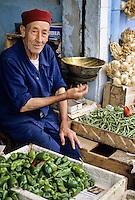 Tunis, Tunisia.  Vegetable Vendor in Neighborhood Market near Bab Souika.  He is wearing a chechia, the traditional Tunisian hat.