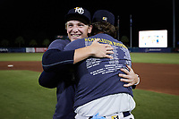 Seth Johnson (left) of the Charleston RiverDogs gets a hug from teammate Graeme Stinson following their win over the Down East Wood Ducks in the 2021 Low-A East Championship game at Joseph P. Riley, Jr. Park on September 26, 2021 in Charleston, South Carolina. (Brian Westerholt/Four Seam Images)