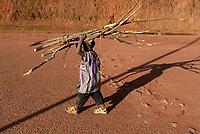 RWANDA, Byumba , boy carry firewood on his head  / RUANDA, Byumba, Junge traegt Feuerholz auf dem Kopf