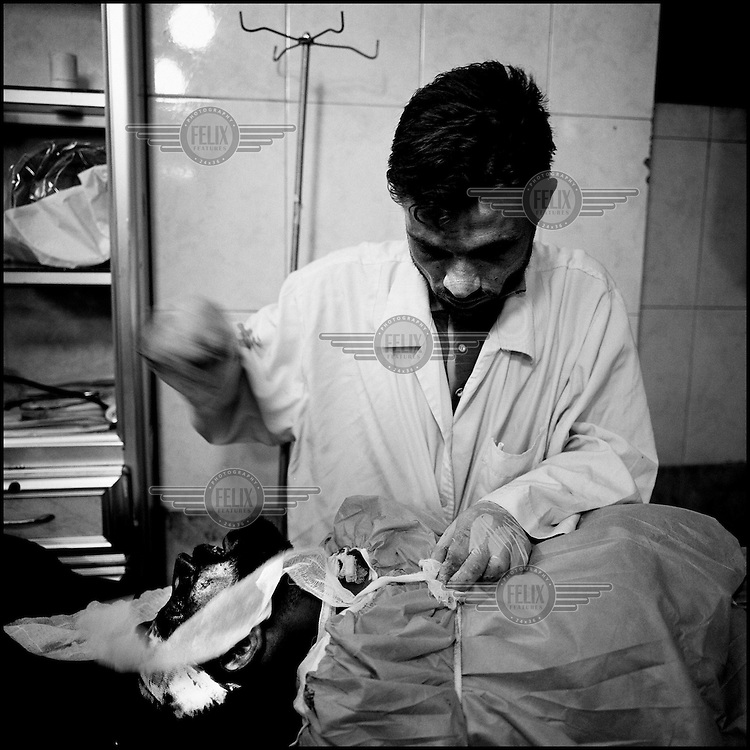 Syria/Aleppo/Aug 29,2012/  A man from the medical staff of the Dar al-Shifa hospital prepaires the body of a rebel to give it to his relatives. The rebel died during  airstrike bombings.Over 60,000 of Syrians have died since the uprising began in March 2011 and  more than 500,000 of Syrian refugees have fled the country to neighboring Turkey,Lebanon,Jordan and Iraq.Giorgos Moutafis