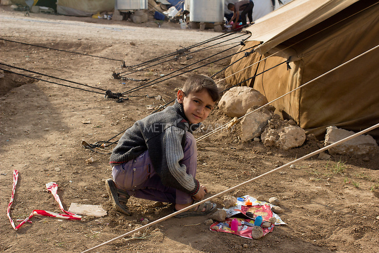 DOMIZ, IRAQ: A Syrian refugee plays with colored paper and rocks outside his tent in the Domiz refugee camp in the Kurdish region of northern Iraq...The semi-autonomous region of Iraqi Kurdistan has accepted around 60,000 refugees from war-torn Syria. Around 20,000 refugees live in the Domiz camp which sits 60 km from the Iraq-Syria border...Photo by Younes Mohammad/Metrography