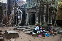 Cambodia.  Ta Prohm Temple Ruins, 12th-13th. Century.  Young Boys Selling Souvenirs, Trinkets, and Postcards.