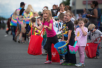 Kids beg parade participants to throw candy during the Bear Paw Festival Grand Parade in downtown Eagle River.