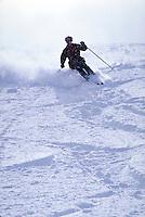 Backlighted snow skier cuts through deep, light powder on an open slope. Utah, Alta Ski Resort.