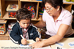 Education preschool 3-4 year olds female teacher working with boy on pre-writing activity tracing letters of his name with a marker horizontal
