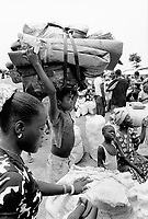 """Guinea. State of """"Guinée Forestière"""". Parrot's beak. Kolomba. Camp for Sierra Leoneans refugees. Young boy carries on his head the family belongings before boarding one of the UNHCR trucks which soon will leave in convoy the camp and the area. UNHCR's (United Nations High Commision for the refugees)  decision is to carry out the refugee evacuation movement out of the troubled camps of the """"Parrot's beak"""" region for a relocation in safer camps. © 2001 Didier Ruef"""