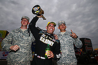 Feb 22, 2015; Chandler, AZ, USA; NHRA top fuel driver Tony Schumacher celebrates with US Army soldiers after winning the Carquest Nationals at Wild Horse Pass Motorsports Park. Mandatory Credit: Mark J. Rebilas-