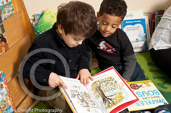 Education Preschool Headstart 3-4 year olds two boys sitting together and looking at book, talking