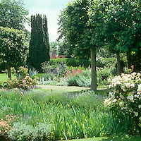 A view across the extensive flowerbeds of the garden with the house just visible in the background
