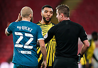 Troy Deeney of Watford has words with Teemu Pukki of Norwich City and Referee John Brooks during the Sky Bet Championship behind closed doors match played without supporters with the town in tier 4 of the government covid-19 restrictions, between Watford and Norwich City at Vicarage Road, Watford, England on 26 December 2020. Photo by Andy Rowland.