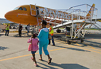 Adrian Scott walks with her children to the inaugural flight of Skybus Airlines in Columbus, Ohio, Tuesday, May 22, 2005. Scott bought her family's tickets for $10 each.  Skybus Airlines Inc., will compete with Southwest Airlines Co., JetBlue Airways Corp. and other low-cost companies.