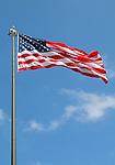 American flag on pole against a blue sky background.