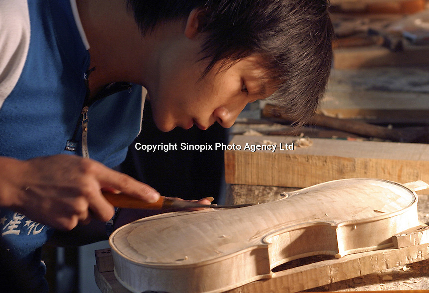 A Chinese craftsman carves the exterior of an unfinished violin at the Shanghai Wellsound-Tianyin Violin Factory  in Shanghai, China. Started in 1992 by a family with four generations of music instruments making experience, the company exports most of its high-end and hand crafted string instruments overseas. China supplies over 90% of the world's high-end music instruments..13-SEP-04