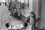 Young white girl playing with two black child's dolls in a pram Glasgow. Scotland UK.  She is waiting outside a shop while her mother is inside doing the shopping. 1979